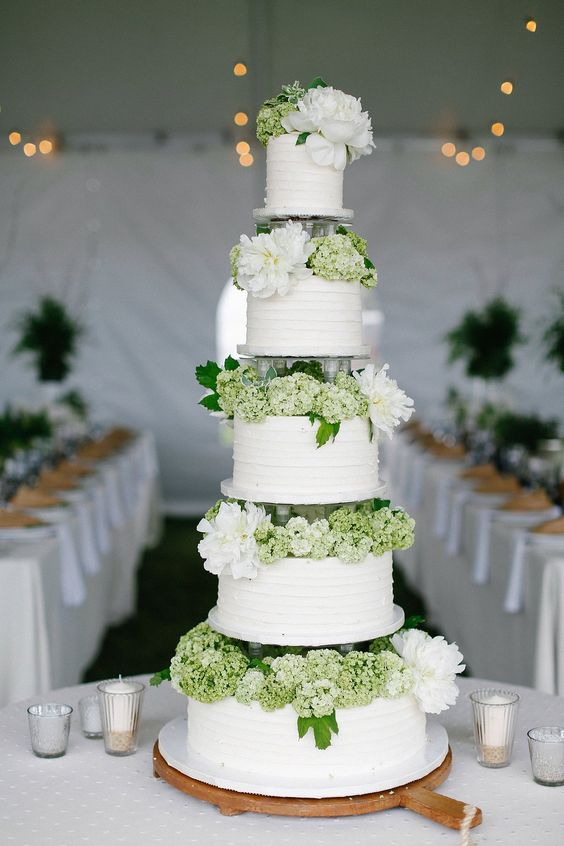 a rustic white wedding cake with textural tiers, green and white blooms between the tiers
