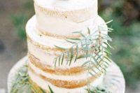 a semi naked wedding cake topped with a cactus and decorated with greenery for a desert wedding