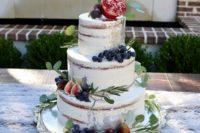 a semi naked wedding cake topped with fresh greenery and fruits on top for a cool fall wedding
