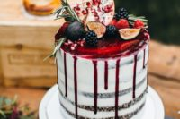 a semi naked wedding cake with pomegranate drip topped with fruits and greenery for a decadent fall wedding