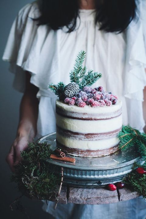 a semi naked wedding cake with sugared cranberries and pinecones on top is perfect for a winter or Christmas wedding
