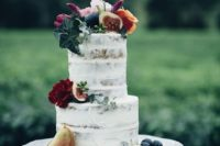 a simple semi naked wedding cake with fruits and foliage on top plus some bold blooms for a fall wedding