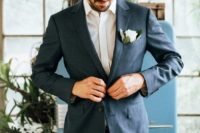 a simple wedding outfit with a white shirt, a navy jacket and ta pants plus a single white bloom in the pocket