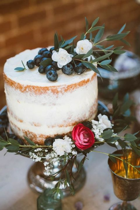 a small naked wedding cake topped with blueberry and flowers plus some greenery is awesome for a spring or summer wedding