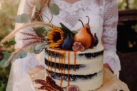 a statement fall naked wedding cake of chocolate, with pears, figs, greenery and blooms on top and some caramel drip