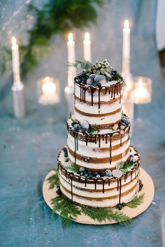 a statement naked wedding cake with sugared berries, greenery, silver chocolate coins and chocolate drip