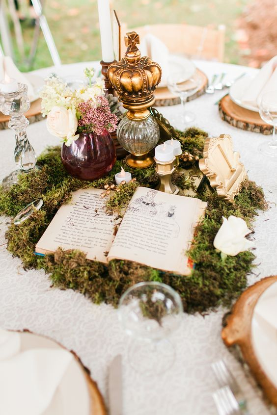 a story book wedding centerpiece composed of moss, a story book, candles, a crown on a stand and a floral arrangement