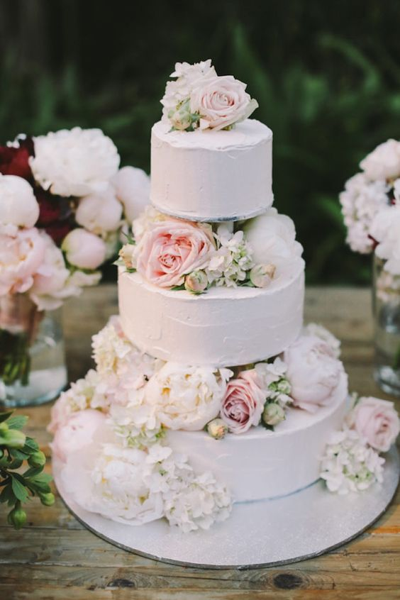 a subtle white textural wedding cake with white and blush blooms is very tender and cute