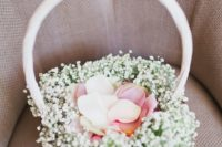 a white basket decorated with baby's breath and with petals inside is a classic option