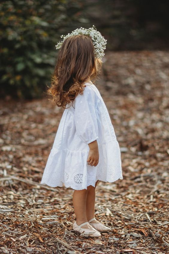 a white cotton A-line knee dress with short sleeves and a lace skirt plus sandals and a baby's breath crown