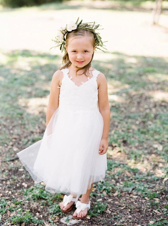a white midi dress with a tulle skirt, a lace bodice with thick straps, sandals and a greenery crown