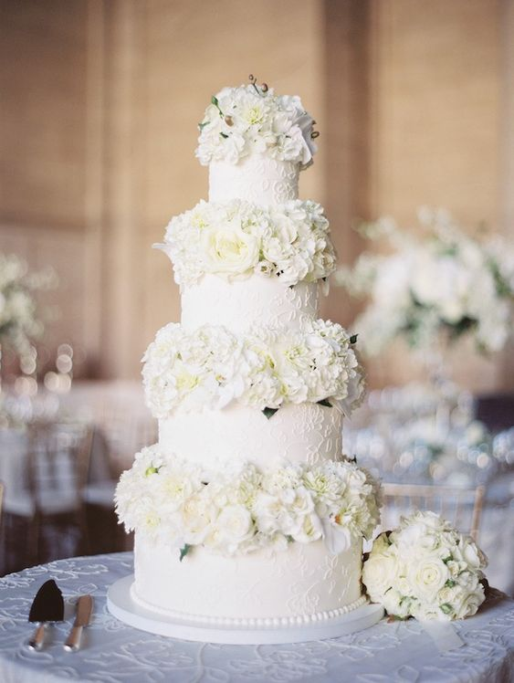 a white patterned wedding cake with white blooms between the tiers is very elegant and very chic