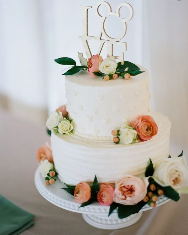 a white textural wedding cake with fresh blooms and a Mickey Mouse LOVE topper