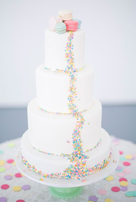 a white wedding cake decorated with colorful sprinkles and confetti and with bold macarons on top for more fun