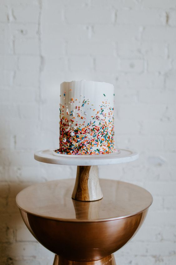 a white wedding cake with a textural edge and colorful sprikles coming up for a modern fun wedding