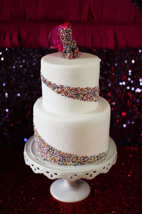 a white wedding cake with sprinkle patterns and a bold sprinkle pony topper with pink hair for fun
