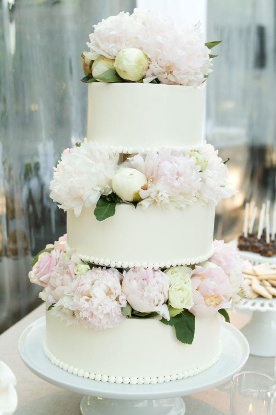a white wedding cake with white and blush blooms and leaves between the tiers is wow