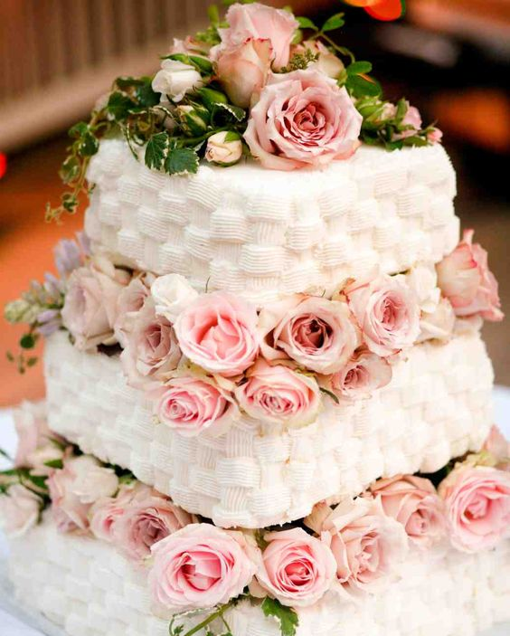 a white woven buttercream wedding cake with pink roses and greenery between the tiers and on top the cake