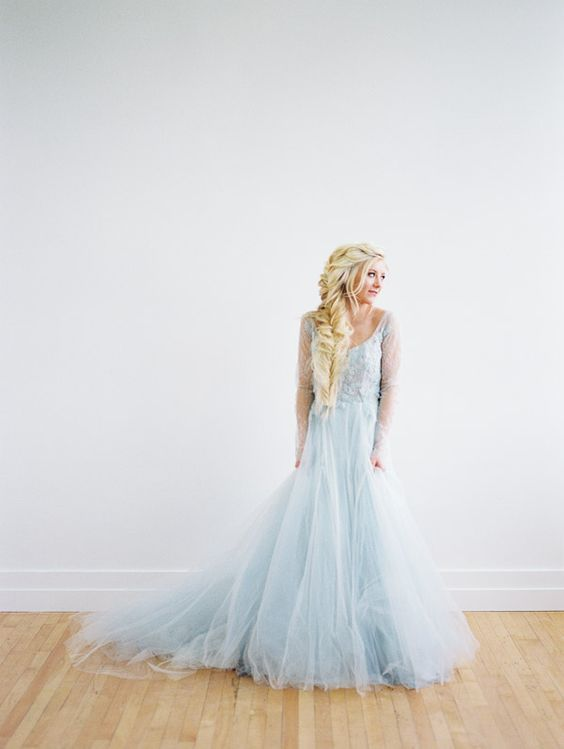 an Elsa inspired bridal look with a blue wedding dress with a scopp neckline and a tulle skirt plus a dimensional loose Elsa braid