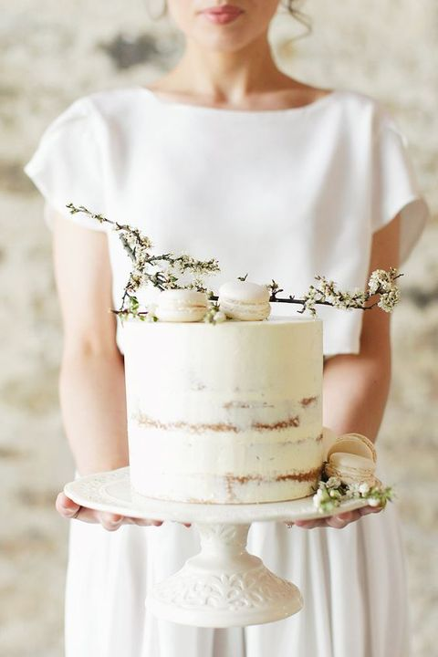an ethereal white semi naked wedding cake topped with macarons and flowers is amazing for a spring wedding