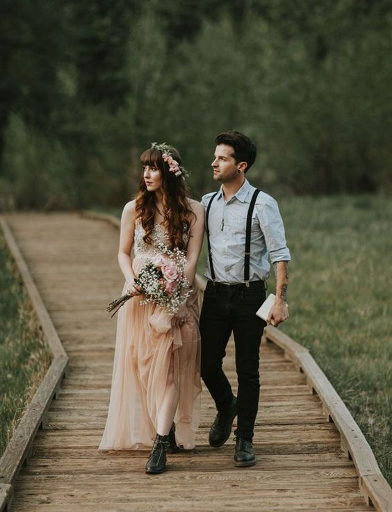 an informal meets boho groom's look with a light blue shirt, black jeans and suspenders and black shoes