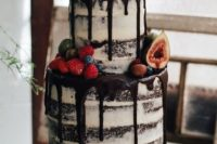 semi naked chocolate wedding cake with chocolate drip topped with fruit and berries is amazing for summer or fall