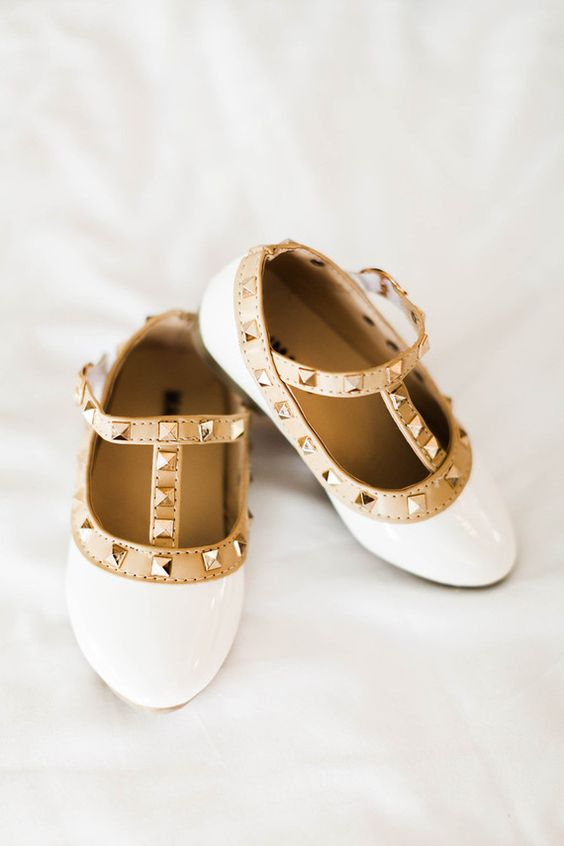 shiny white flats with tan straps and studs are a very trendy and bold option to rock