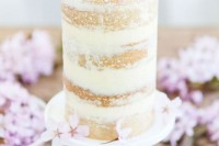 a tall naked wedding cake with tender pink blooms on top looks very chic and very romantic