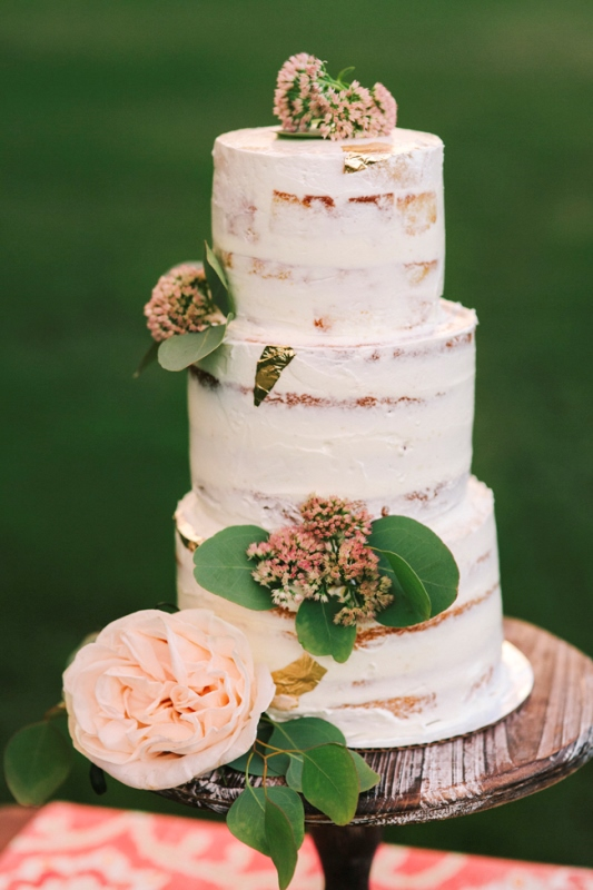 a naked wedding cake with pink blooms and leaves is a nice idea for a spring or summer wedding