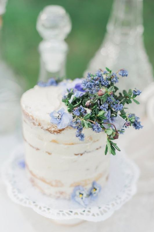 a spring or summer naked wedding cake topped with blue blooms is a cool idea for a pastel wedding