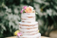a naked wedding cake with bright blooms on top and citrus is a nice idea for a summer or tropical wedding