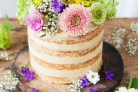 a naked wedding cake topped with greenery and bright flowers is a nice idea for a colorful spring or summer wedding