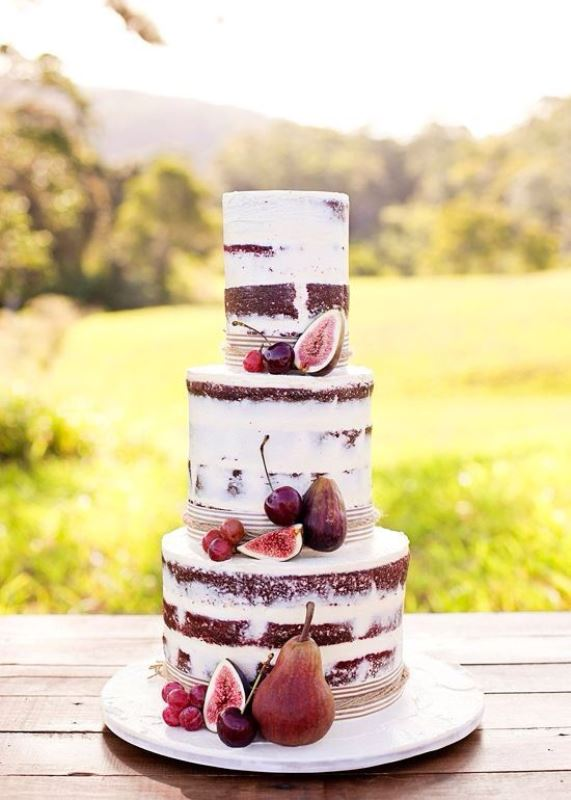 a fall chocolate naked wedding cake with cherries, pears and figs is a nice idea for a fall wedding