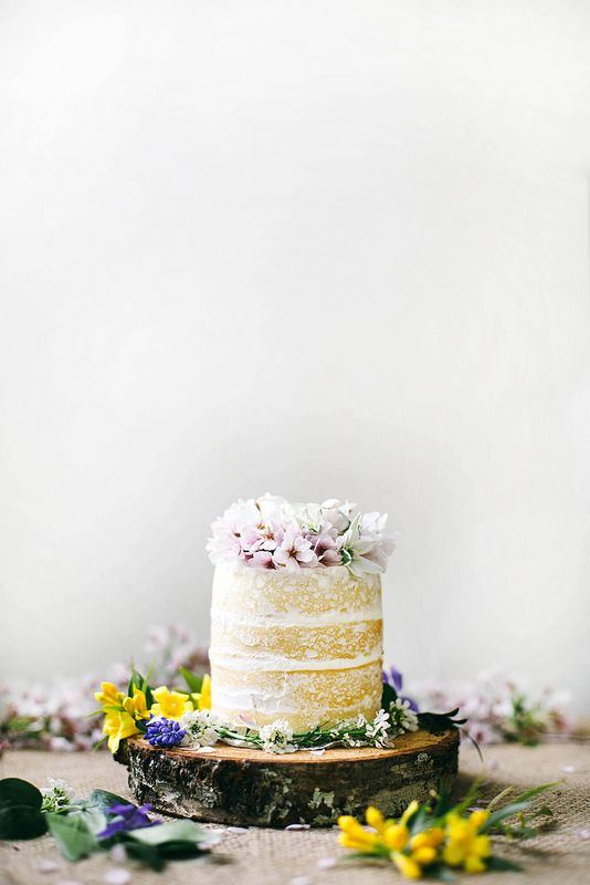 a naked wedding cake topped with fresh pink blooms and served on a wooden slice with colorful wildflowers
