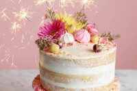 a super bright naked wedding cake with pink and yellow blooms, cherries, sparklers and bright petals and gold leaf
