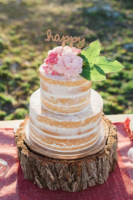 a spring or summer naked wedding cake with pink and blush blooms and leaves is a cool idea