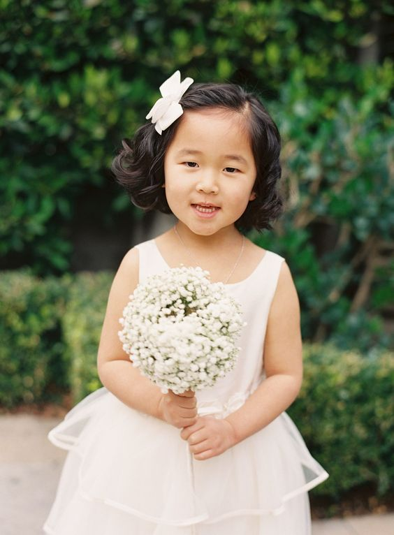waves down, side parting and a white bow on one side are all your flower girl needs to look fantastic