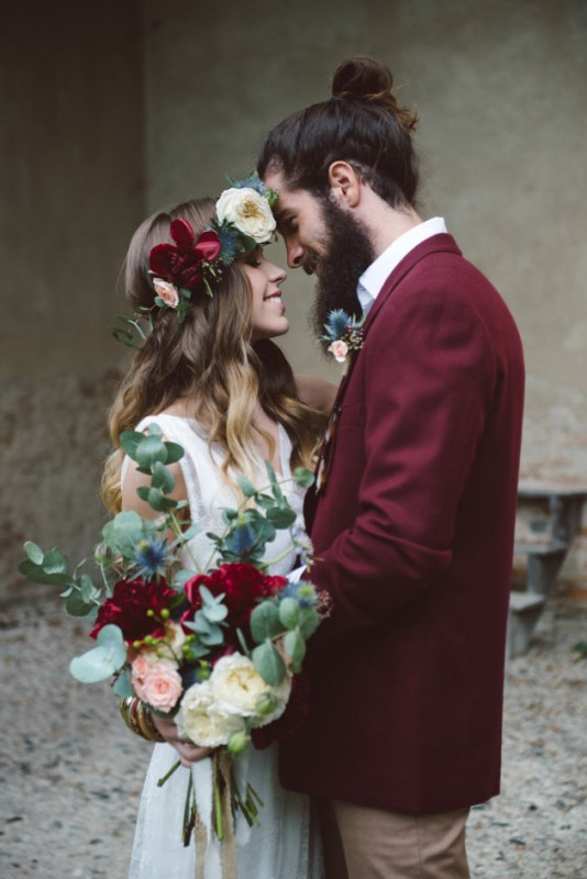 a boho groom's look with a burgundy blazer, tan pants, a white shirt and a man bun plus a full beard to look really bold and cool