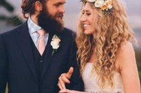 a summer boho groom's look with a three-piece grey pantsuit, a pink tie, a full beard and a man bun is bold and chic