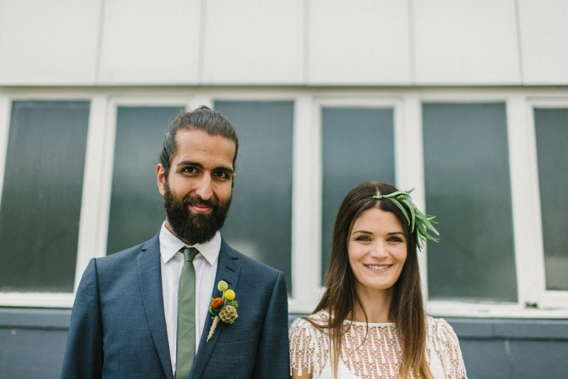 a grey suit, a white shirt,a  green tie, a full beard and a man bun for a stylish and chic boho groom look