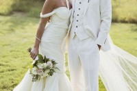 a white three-piece wedding suit, a white shirt, brown shoes, a green boutonniere and a trendy man bun to give a fashion-forward look to it