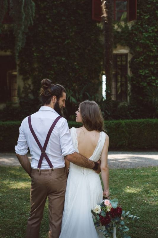 tan pants, a white shirt, burgundy suspenders, a full beard and a man bun for a simple and cool boho groom's look