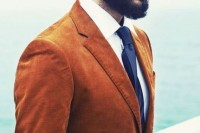 a rust-colored velvet blazer, a navy tie, a white shirt, a full beard and a man bun for a bold boho look – try it for a fall wedding