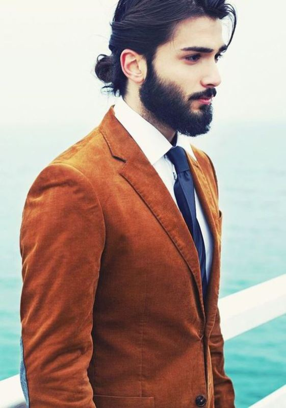 a rust-colored velvet blazer, a navy tie, a white shirt, a full beard and a man bun for a bold boho look - try it for a fall wedding