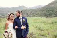 a navy blazer, purple velvet pants, a striped tie and a white shirt, a full beard and a man bun for a lovely boho groom's outfit