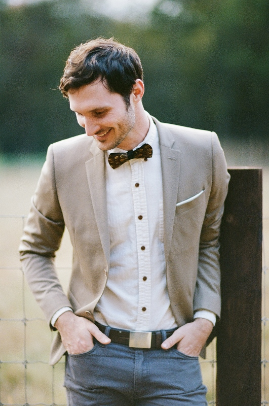 an elegant barn groom look with a camel blazer, a white shirt with black buttons, grey pants, a burgundy bow tie and a brown belt