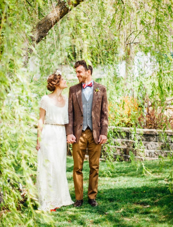 an elegant and chic groom's look with mustard pants, a grey waistcoat, a muted red blazer, a bright red bow tie