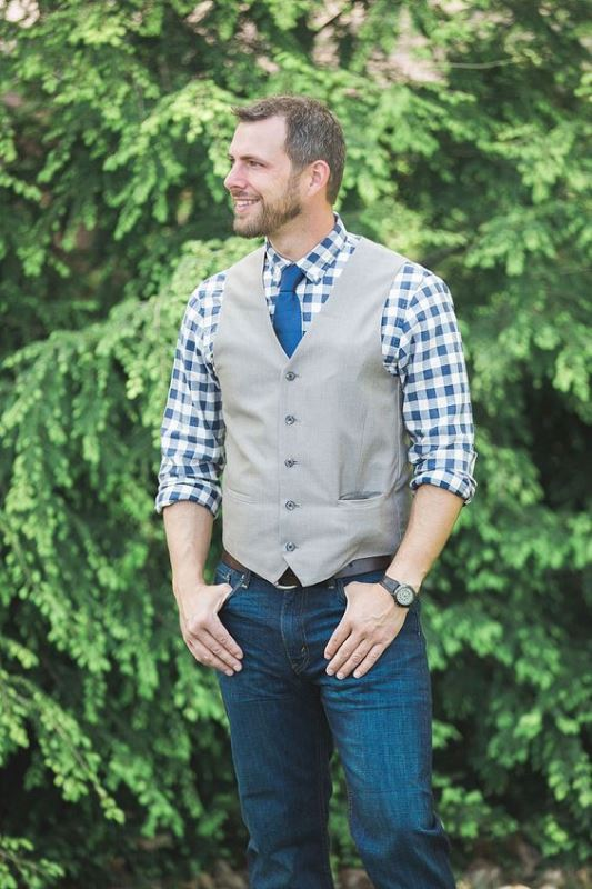 a relaxed barn groom's look with jeans, a checked button down, a grey waistcoat and a bright blue tie