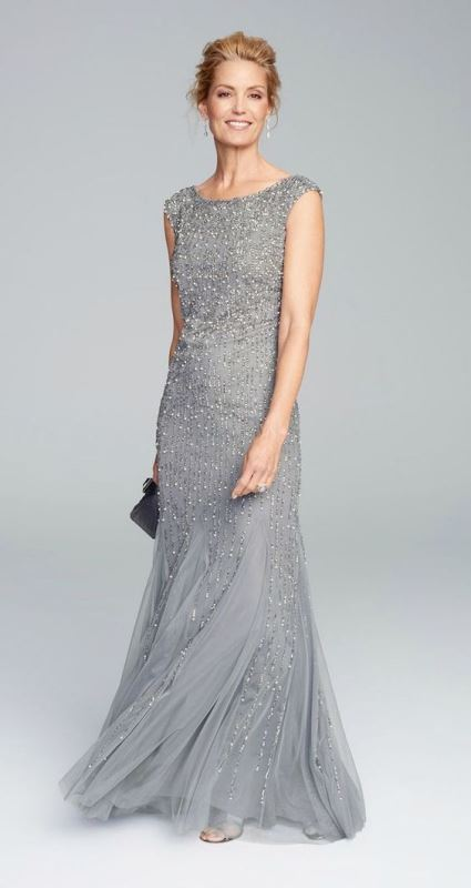 a heavily embellished grey maxi dress with a high neckline and no sleeves looks very festive and sparkling