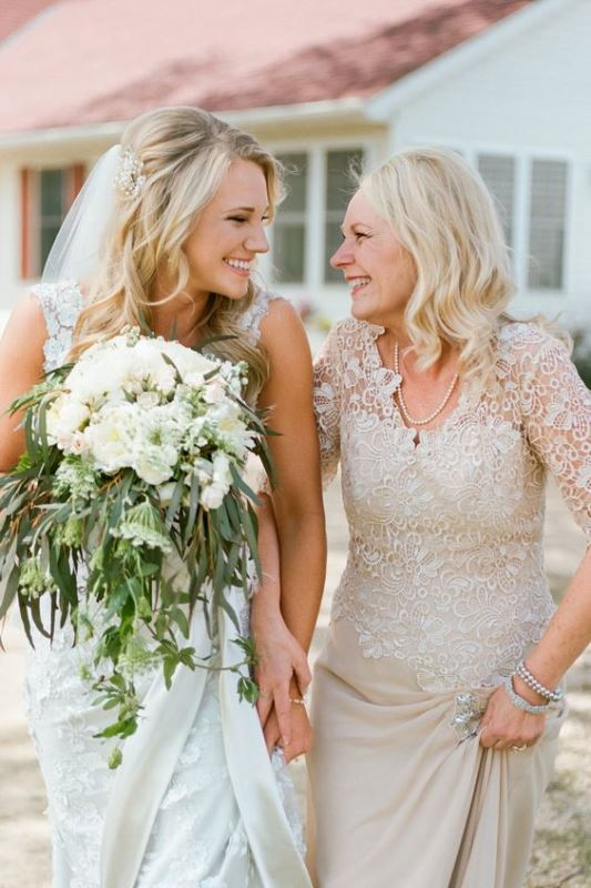 a neutral mother of the bride dress with a lace bodice with long sleeves and a plain skirt